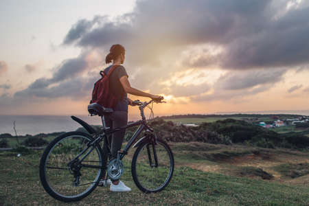 Young woman watching the sunset and the beautiful view of nature while standing with her bicycle on a hill.