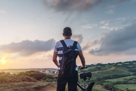 Young man in the evening at sunset standing on a hill with a bicycle Standard-Bild