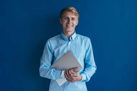 Portrait of blonde guy with laptop wearing casual shirt smiling and looking in camera