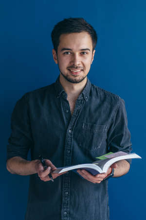 Cheerful man with open book in his hands smiles happily, dresssed casually. Standard-Bild