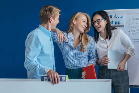 Portrait of business team standing together and laughing