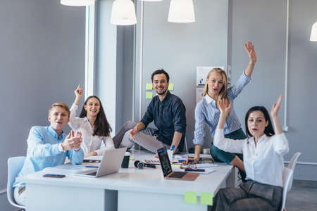 Group of young business people at a table waving their hands cheerfully as they look at the camera Standard-Bild