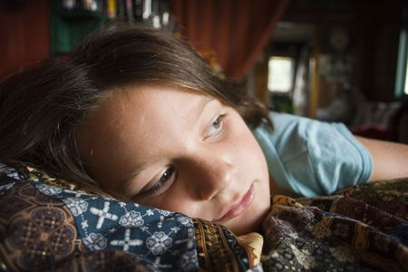 Girl laying on bed contemplating Einsteins theory of relativity Stock Photo
