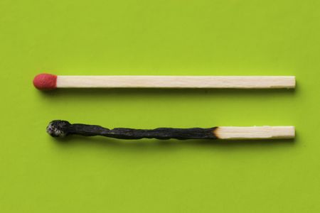 A burnt match and a live match lay side by side in harmony Stock Photo