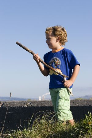 aotearoa: A boy plays beside an old concrete bunker with a stick for a gun.