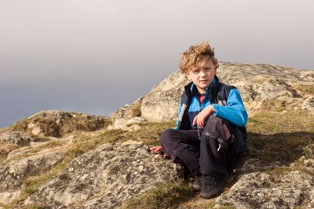 Te: A boy sits on top of Te Mata Peak, a 399-metre outcrop, which according to local Maori legend is the body of a giant, Te Mata o Rongokako. Te Mata peak is situated in Hawkes Bay, New Zealand. The range is limestone sea bed that has been pushed up over 50 Stock Photo
