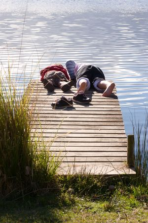 kids stare into the water at the end of a jetty on Lake Tutira, Hawkes Bay, New Zealand