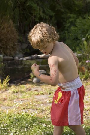 muscle boy: Boy with a super-cool dinosaur tattoo designed by his older brother Stock Photo