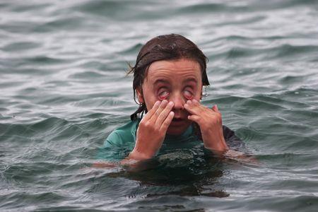 Boy has sore eyes after swimming in the salt water at Rangitoto Island, Hauraki Gulf, New Zealand photo