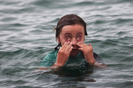 Boy has sore eyes after swimming in the salt water at Rangitoto Island, Hauraki Gulf, New Zealand photo
