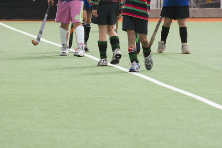 Kids standing on artificial turf playing hockey Stock Photo