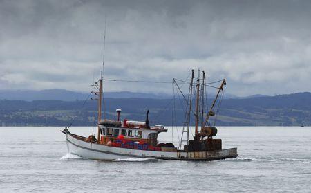tug boat: A rusty fishing boat chugs along the Hauraki Gulf in New Zealand Stock Photo