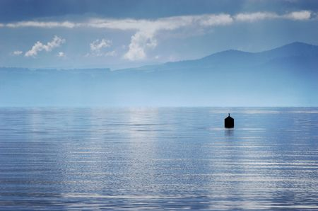aotearoa: A buoy sits in Lake Taupo shrouded by stormy weather. Taupo, New Zealand Stock Photo