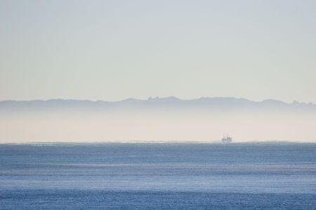 Mist over the ocean with a fishing boat photo