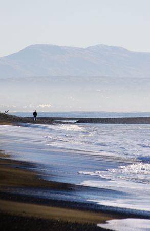 A walker strolls along Haumoana Beach in Autumn photo