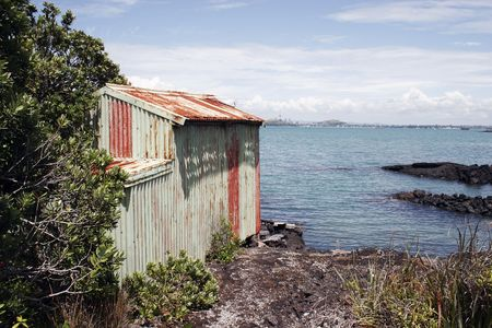 sun  soaked: A weathered boat shed sits on the rocky shore of Rangitoto Island, Hauraki Gulf, New Zealand