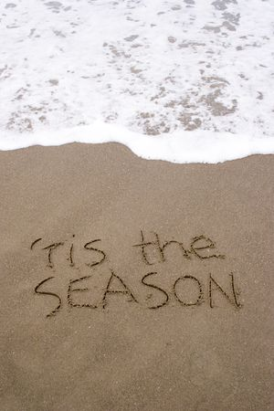 christmas tide: tis the season written in the sand. A summer Christmas in the Southern Hemisphere. Stock Photo