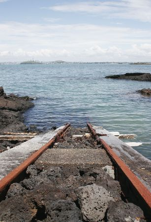 sun  soaked: A train track runs from a boat shed into the water of the Hauraki Gulf Stock Photo