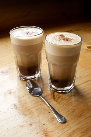 The morning coffee with steamed milk in glass cups on a wooden bench