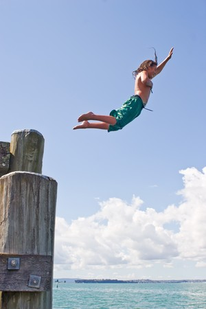 A teenage boy leaps off the wharf at Rangitoto Island in the Hauraki Gulf of New Zealand