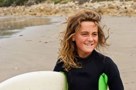 A young male about to surf at Waimarama Beach, Hawkes Bay, New Zealand