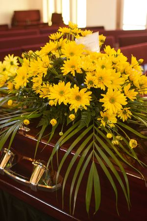 Flowers from the family on a casket at a funeral.