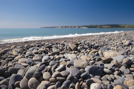 new zealand beach: Stones on Haumoana Beach with Cape Kidnappers in the background Stock Photo