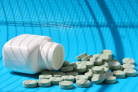 Small bottle with the scattered tablets against a shadow from a lattice  Stock Photo