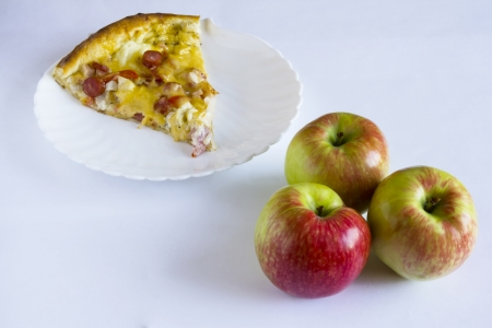 Apples against a piece of  pizza on a plate