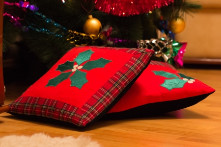 Christmas pillows on a floor with a christmas tree.