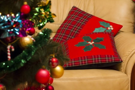 Christmas pillows on an arm-chair with a christmas tree. Stock Photo