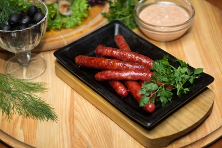 Fried sausages in a frying pan on a wooden background Stock Photo