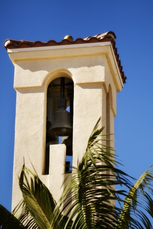 California Mission Church Bell Tower with Palm Tree against a Bright Blue Sky