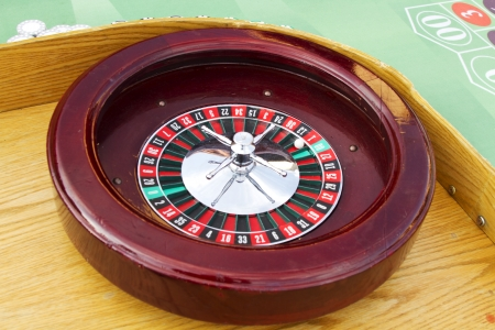 A Cherry Wood Roulette wheel surrounded on a Professional Roulette Table  The ball is on red 1  Imagens