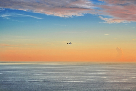 Small plane fly across the ocean at sunset