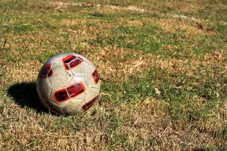 Soccer ball on dry field in sunny day at suburb of Thailand photo