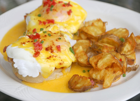 uk cuisine: English breakfast Eggs Benedict. Muffins, bacon, poached eggs, and buttery hollandaise sauce serve with potato fries