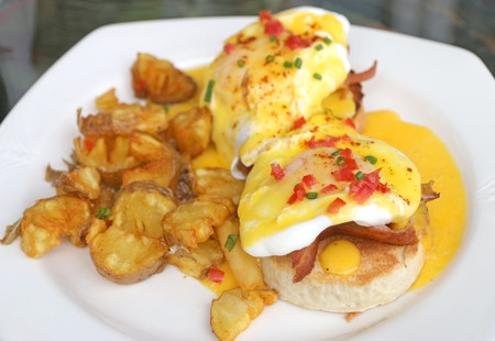 buttery: English breakfast Eggs Benedict. Muffins, bacon, poached eggs, and buttery hollandaise sauce serve with potato fries