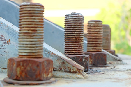 Big rusty metal nuts locked with rust and corrosion bolts