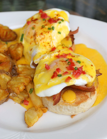 buttery: English breakfast Eggs Benedict. Muffins bacon poached eggs and buttery hollandaise sauce serve with potato fries Stock Photo