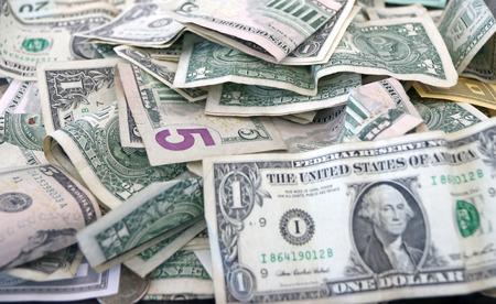 pennie: Pile of America dollar bills in donation box.