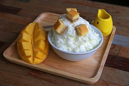 serve: Milk Bingsu (shaved ice) cheese topping serve with mango, Korean dessert