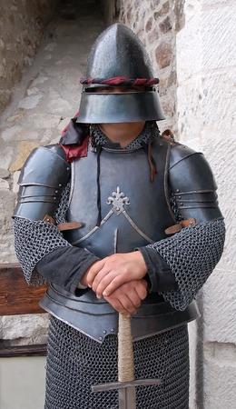 Standing medieval sergeant with helmet protect the door.