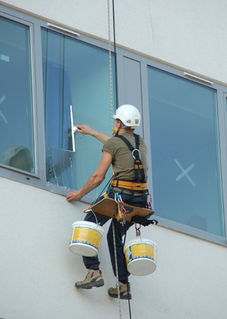 Window washers cleaning outside working on a building Stock Photo