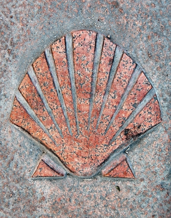 pilgrim journey: In Spain this symbol shows the right way to the final destination (Santiago de Compostela) on the Camino de Santiago route and its old town has the UNESCO World Heritage designation.  Stock Photo