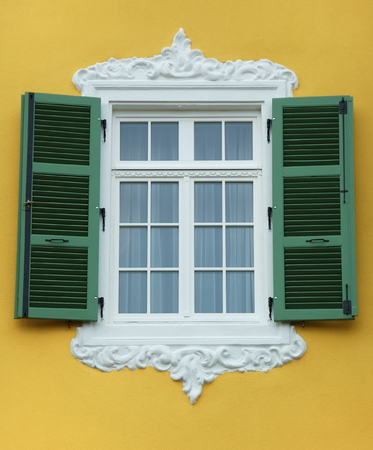 Arabesque window frame with open green shutter, yellow wall. Stock Photo