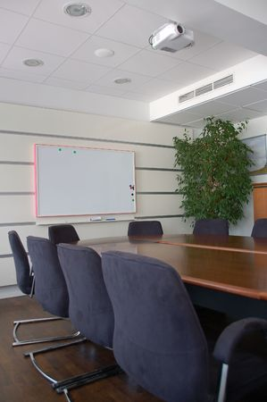 Office empty meeting room with white blackboard and projector.
