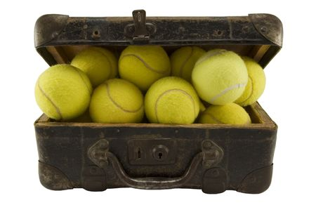 Old brown suitcase full of tennis balls isolated on white. Stock Photo