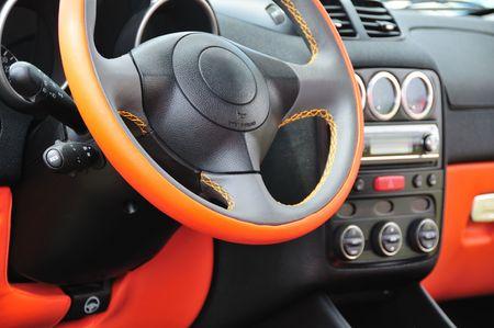 Modern car interior with orange steering wheel. Stock Photo