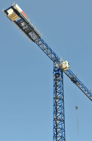 erect: Blue construction crane with blue clear sky.
